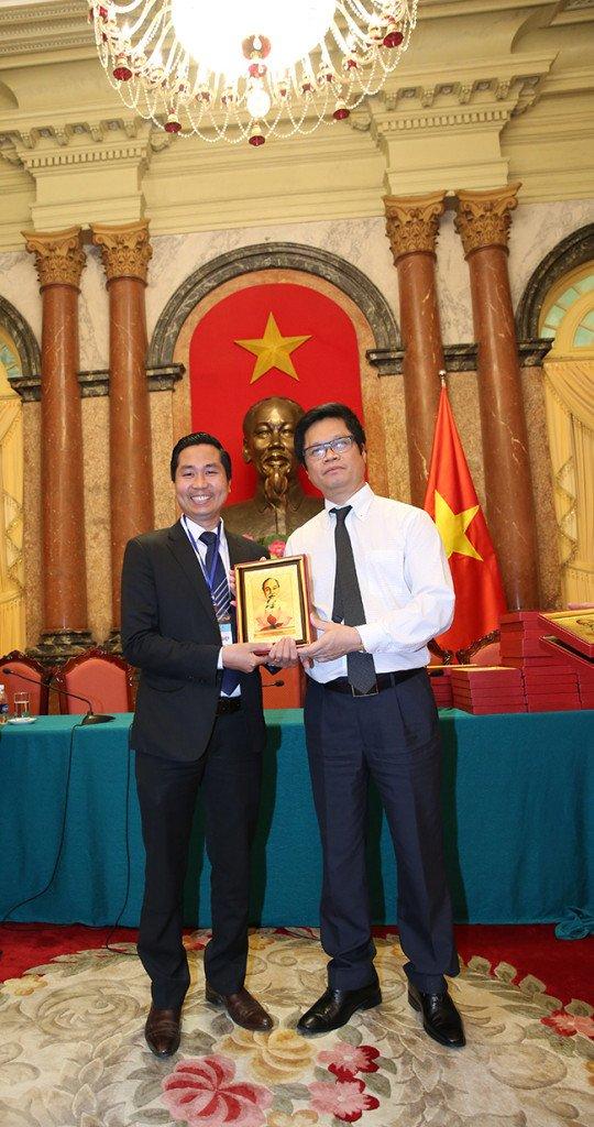 Ông Vũ Tiến Lộc chủ tịch VCCI đại diện cho phủ chủ tịch trao quà cho doanh nhân Nguyễn Bá Toàn